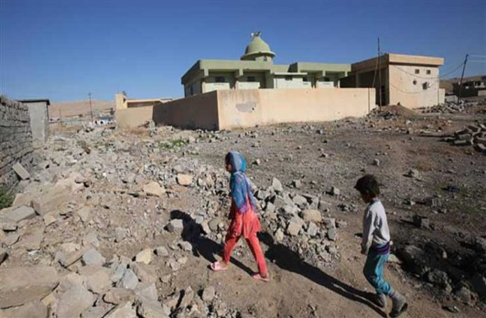 Iraqi children from the Shabak community walk past their house, which was destroyed by the Daesh Takfiri terrorists, in the village of Baz Gerkan east of Mosul, northern Iraq, January 10, 2018. (Photo by AFP)