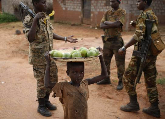 A boy carries oranges to sell to Seleka fighters in a village between Bambari and Grimari