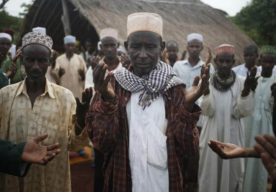 Muslim men from Puel tribe pray in a village outside Bambari